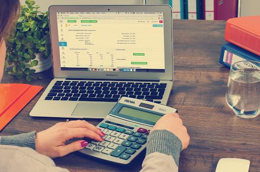 Mulher calculando quanto custa abrir uma empresa